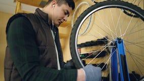 被集中的技工修理在自行车车轮的轮幅有特定工具的,当为自行车服务和听到音乐时 影视素材