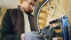 被集中的技工检查然后修理轮幅的转动的自行车车轮与特定工具,当为自行车服务和时 股票录像