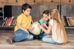被集中的探索地球的男孩和女孩在图书馆里 图库摄影