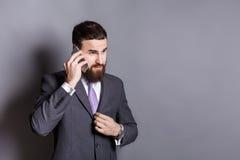 被集中的有胡子的商人谈话在电话 免版税库存照片