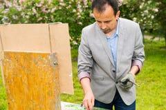 被集中的男性中间agedpainter绘画在庭院里 库存照片