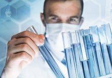 被集中的男性科学家画象与试剂一起使用在实验室 库存照片
