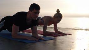 被集中的白种人担任在瑜伽席子的人和白肤金发的女孩板条职务,当训练户外,在海附近时 股票录像