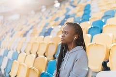 被集中的美国黑人的少年的特写镜头旁边画象观察比赛,当坐体育场时 免版税图库摄影