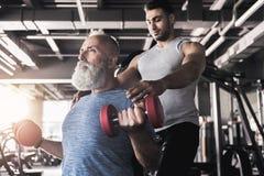 被集中的资深男性训练他的在健身房的二头肌 免版税库存图片