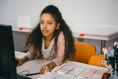 被集中的非裔美国人的女小学生与计算机一起使用 库存照片
