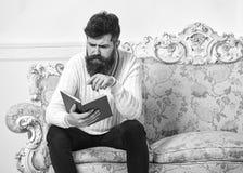 被集中的面孔阅读书的强壮男子 诽谤性的畅销书概念 人与注意的阅读书 刮胡须人 库存图片