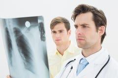 被集中的医生和耐心审查的肺X-射线 图库摄影