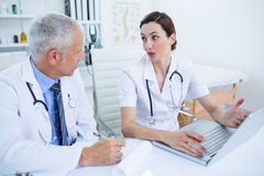 被集中的医疗同事谈论和与膝上型计算机一起使用 库存图片