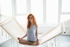 被集中的年轻红头发人夫人坐吊床思考 免版税库存照片