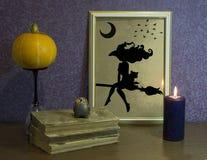 被雕刻的万圣节南瓜 神秘魔术书  框架和灼烧的蜡烛 免版税库存图片