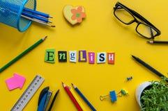 被雕刻的信件的英国词在黄色背景的与办公室或学校用品,学会概念的英语 免版税图库摄影