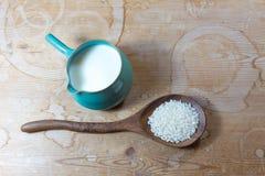 被雕刻的木匙子用在一个绿色陶瓷碗投手的米在土气木桌背景的米牛奶旁边 免版税库存照片