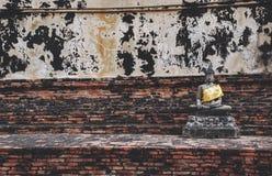 被雕刻的石菩萨雕象在阿尤特拉利夫雷斯有砖墙背景 免版税库存图片