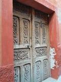 被雕刻的古色古香的木门和土气墨西哥灰泥门道入口有布朗和铁锈织地不很细墙壁背景 库存照片