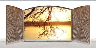 被雕刻的木双门有在日落的湖视图 免版税库存图片