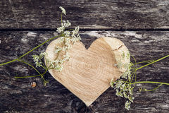 被雕刻的木心脏和白花在老公猪背景  免版税库存图片
