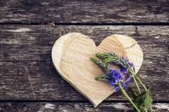 被雕刻的木心脏和蓝色花在老委员会背景  库存照片