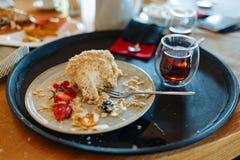 被鞭打的奶油蛋糕、一杯茶和在一个黑圆的盘子的一把匙子被咬住的片断在咖啡馆的一张桌上 免版税图库摄影