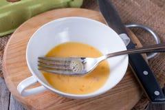 被鞭打的蛋黄用在一个玻璃碗的糖 库存照片