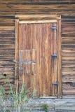 被风化的土气木棚子门 库存图片