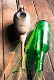 被风化的油罐头,玻璃瓶和草在木 库存图片