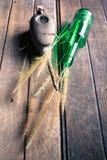 被风化的油罐头,玻璃瓶和草在木 免版税库存照片
