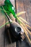 被风化的油罐头,玻璃瓶和草在木 图库摄影