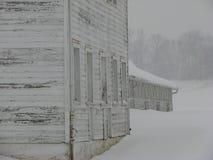 被风化的谷仓在一个多雪的多云冬日 免版税库存图片