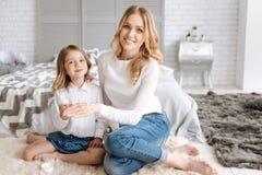 被绘在她的母亲手上的女儿一张兴高采烈的面孔 库存图片