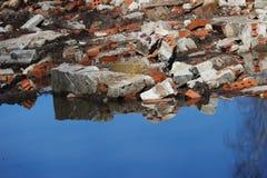 从被破坏的古老大厦的墙壁的砖片断在一个水坑在公园 Gatchina俄罗斯 免版税库存照片