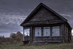 被破坏的房子放弃了朝阳的背景的村庄 免版税库存图片