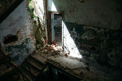 被破坏的黑暗内部在阳光下放弃了大厦,门 图库摄影