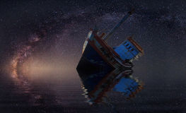 被击毁的船在与明显地银河的繁星之夜下 库存照片