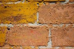 被绘的和剥落的砖墙的宏观图象 库存照片