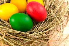 被绘的复活节彩蛋在干草巢在  免版税库存图片