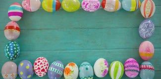 被绘的复活节彩蛋在木板条的长方形形状安排了 免版税库存图片