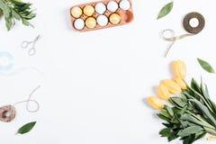 被绘的鸡蛋、郁金香、绳索、丝带、剪刀和地方文本的 免版税库存图片