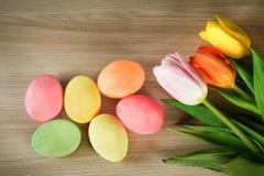 被绘的鸡蛋和春天上色了木表面上的郁金香 免版税库存图片