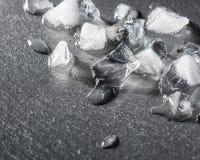 被击碎的冰片断在一块黑石头的 水和寒冷下落  免版税库存图片
