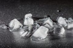 被击碎的冰片断在一块黑石头的 水和寒冷下落  免版税图库摄影