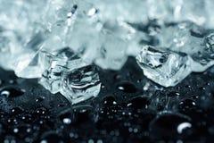 被击碎的冰片断在黑背景的用水下降 免版税库存图片