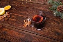 被仔细考虑的酒、拳打和香料glintwine的在葡萄酒木桌背景 图库摄影