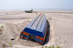 被翻转的蓝色在Konkan上色了在一个海滩的小船 免版税库存图片