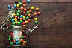 被翻转的玻璃瓶子充分五颜六色的甜点 免版税图库摄影