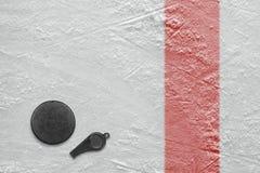 裁判员口哨和冰球 免版税库存照片