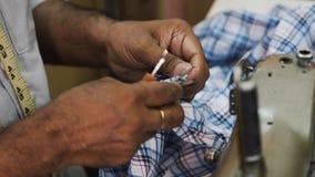 裁缝在商店削减坐在缝纫机的错误线 股票视频