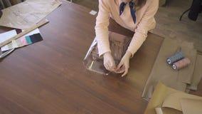 裁缝在缝合的演播室包装衣裳的少妇,站立在桌上,专家在木书桌上工作, 股票录像