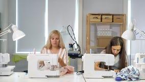 裁缝在车间缝合的衣裳的工作在缝纫机,侧视图 股票录像