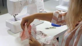 裁缝在车间缝合的衣裳的工作在缝纫机 股票录像